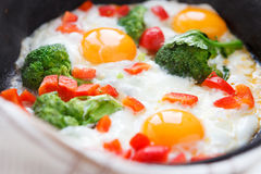 Fried eggs in a frying pan with broccoli and peppers Stock Photos