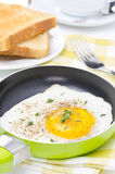 Fried eggs in a frying pan, crisp toast, coffee and orange juice Royalty Free Stock Images