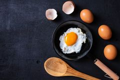 Fried eggs in a frying pan and egg shell for breakfast on a bla royalty free stock photos