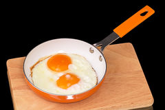 Fried eggs in a frying pan orange Stock Photography