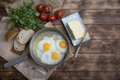 Fried eggs in a frying pan with tomatoes, milk and butter for breakfast. On a wooden background Stock Images