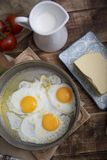 Fried eggs in a frying pan with tomatoes, milk and butter for breakfast. On a wooden background Royalty Free Stock Photo