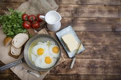 Fried eggs in a frying pan with tomatoes, milk and butter for breakfast. On a wooden background Royalty Free Stock Images