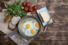 Fried eggs in a frying pan with tomatoes, milk and butter for breakfast. On a wooden background Stock Photo
