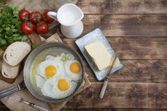 Fried eggs in a frying pan with tomatoes, milk and butter for breakfast. On a wooden background Royalty Free Stock Photos