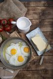 Fried eggs in a frying pan with tomatoes, milk and butter for breakfast. On a wooden background Stock Photography