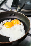 Fried eggs on frying pan Stock Photos