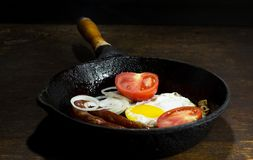 Fried eggs in a frying pan. On wooden background stock photo