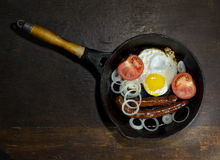 Fried eggs in a frying pan. On wooden background stock photography