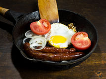 Fried eggs in a frying pan. On wooden background stock photos