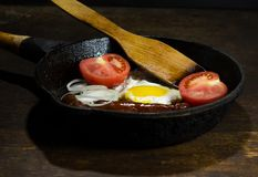 Fried eggs in a frying pan. On wooden background stock image