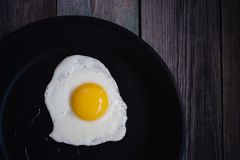 Top view fried eggs in a frying pan on a wooden table. Fried eggs in a frying pan on a wooden table, top view royalty free stock image