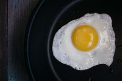 Top view fried eggs in a frying pan on a wooden table royalty free stock photo