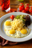 Fried eggs with grated cheese and salad Royalty Free Stock Images