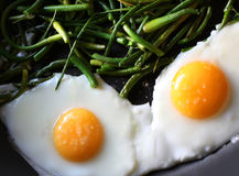 Fried eggs with green beans royalty free stock images