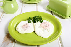 Fried eggs in green ceramic plate Stock Photography