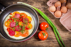 Fried eggs with greens, sausage and tomato. Fried eggs with greens, raw eggs, sausage and tomato slices on pan, wooden background Royalty Free Stock Image