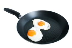 Fried eggs on griddle. Isolated on the white backgroun Royalty Free Stock Photography