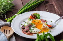 Fried eggs with ham and herbs Stock Photo