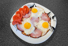 Fried eggs with ham and tomatoes. On the kitchen Royalty Free Stock Photos