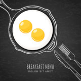 Fried eggs and hand drawn outline watercolor pan, fork and knife. White chalk drawing on black board background.  Royalty Free Stock Image