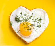Fried eggs in a heart shape with dill Stock Images
