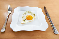 Fried eggs in a heart shape on a white plate and cutlery Royalty Free Stock Photo