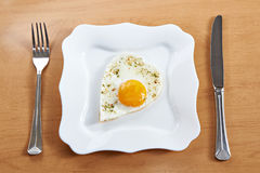Fried eggs in a heart shape on a white plate and cutlery Stock Image