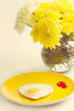 Fried eggs in heart-shaped  of chrysanthemums near Stock Photo