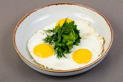 Fried eggs with herbs royalty free stock photography