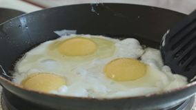 Fried eggs interfere with a spatula in a pan slowmotion. Cooking stock video