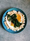 Fried eggs and kale on whole wheat couscous. Sautéed curly green kale and fried eggs with runny yolks are served on top of whole wheat couscous on a blue plate Royalty Free Stock Photography