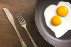 Fried eggs with knife and fork. Two fried eggs in a cast iron skillet on a brown wooden background with knife and fork Stock Photography