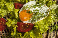 Fried eggs on the leaves of lettuce on a board Royalty Free Stock Images