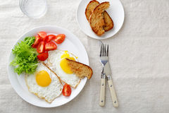 Fried Eggs with lettuce, tomato and bread on a linen tablecloth Stock Images