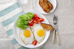 Fried Eggs with lettuce, tomato and bread Royalty Free Stock Images