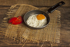 Fried eggs in a little frying pan  on a board Royalty Free Stock Images