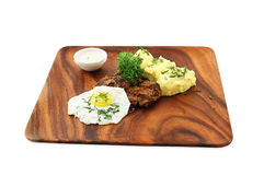Fried eggs with meat. A potato and greens on a wooden dish royalty free stock image
