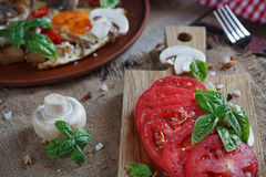 Fried eggs with mushrooms, tomatoes and basil. On rustic background Royalty Free Stock Photography