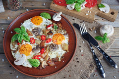 Fried eggs with mushrooms, tomatoes and basil on rustic wooden t. Able. Natural food concept Royalty Free Stock Image