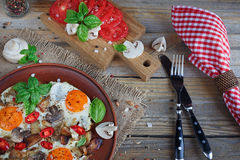 Fried eggs with mushrooms, tomatoes and basil on rustic wooden t. Able. Natural food concept Royalty Free Stock Photography