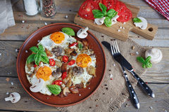 Fried eggs with mushrooms, tomatoes and basil on rustic wooden t. Able. Natural food concept Royalty Free Stock Photo