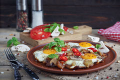 Fried eggs with mushrooms, tomatoes and basil. On rustic wooden table. Natural food concept Royalty Free Stock Photography