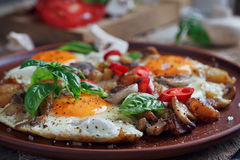 Fried eggs with mushrooms, tomatoes and basil. On rustic wooden table. Natural food concept Stock Images