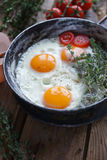 Fried eggs in old frying pan with bread, cherry tomatoes, pepper, oil  and thyme, healthy breakfast Stock Photo