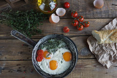 Fried eggs in old frying pan with bread, cherry tomatoes, pepper, oil  and thyme, healthy breakfast Royalty Free Stock Photo