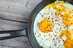 Fried eggs on pan. Fried eggs in cast iron frying pan on gray wooden surface , upper view Royalty Free Stock Photo