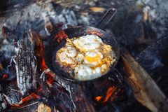 Fried eggs on the pan on the fire in winter stock photos