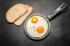 Fried eggs in a pan. Slices of bread Stock Images