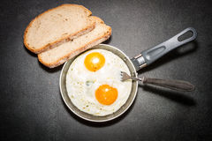 Fried eggs in a pan. Slices of bread Stock Photos